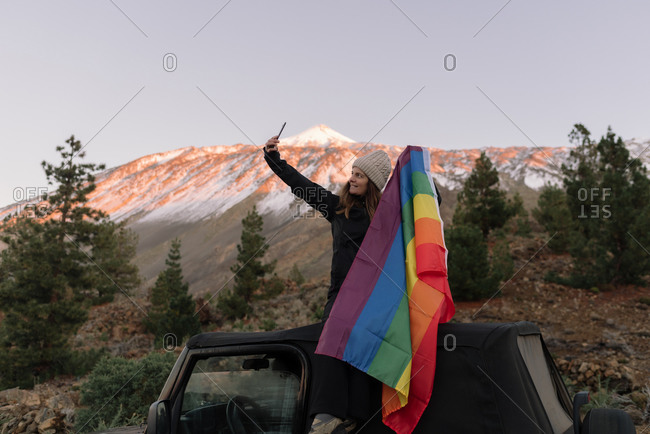 Active woman in warm clothes sitting on black SUV and taking selfie on mobile phone with colorful LGBT flag in mountain in Tenefire, Canary Island, Spain