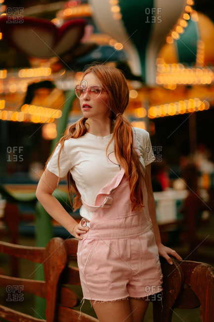 Fashionable female teenager with ponytails and trendy eyeglasses wearing pink jumpsuit and white t shirt standing back to illuminated carousel in amusement park