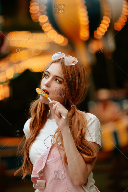 Charming red haired female teenager with ponytails and heart shaped eyeglasses on head standing in amusement park with illuminated attractions and eating lollipop