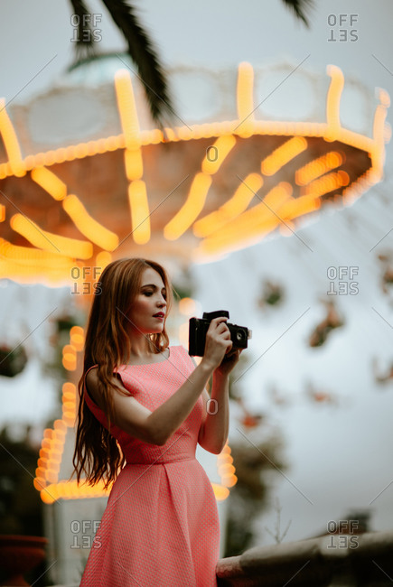 Pretty teenage female wearing charming pink dress taking picture with digital camera while standing next to luminous carousel in amusement park