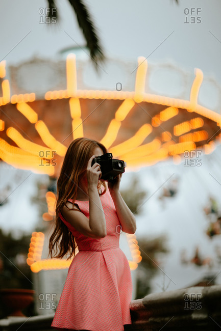 Millennial woman taking picture with camera in amusement park