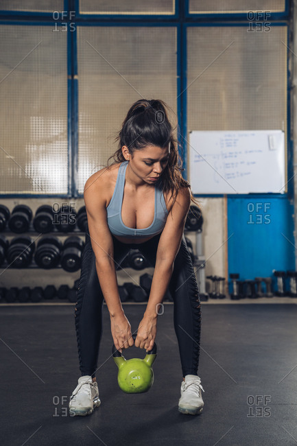 Muscular woman lifting weight in gym