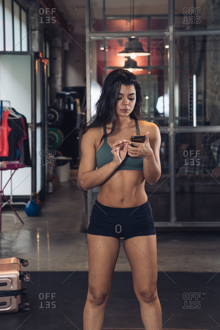 Sportswoman standing in gym with mobile phone