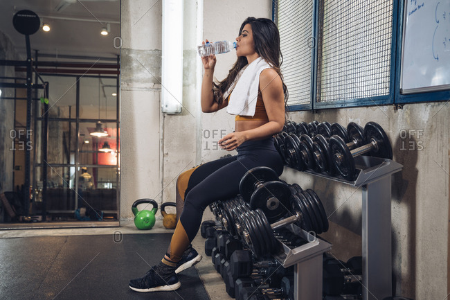 Young sportswoman drinking water in gym