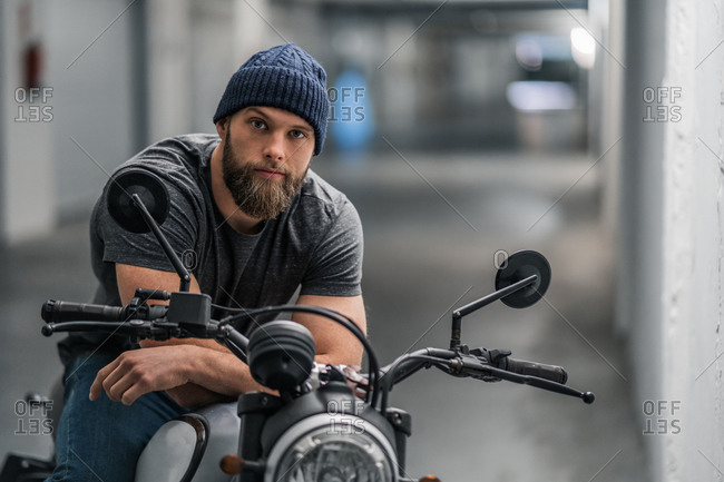 Full body bearded guy in casual clothes sitting on motorcycle and looking at camera in corridor of modern garage