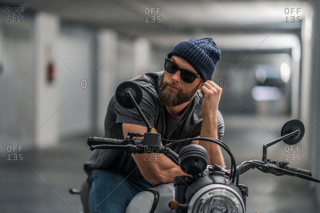 Full body bearded guy in casual clothes and sunglasses on motorcycle in corridor of modern garage