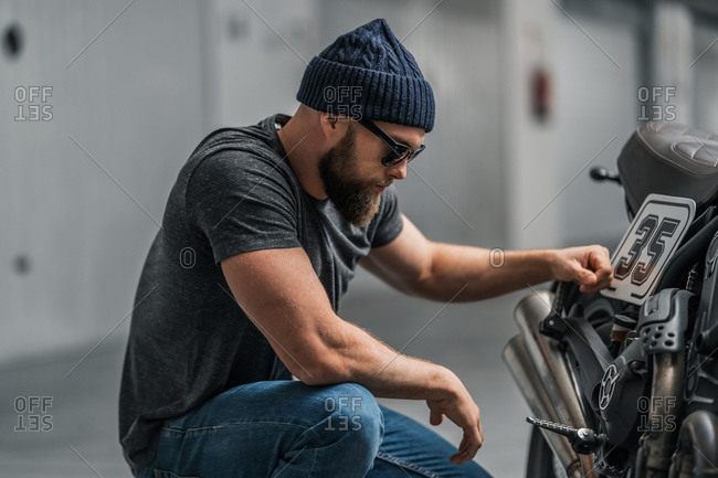 Bearded man in hat raising eyebrow and looking at camera while sitting near motorcycle on blurred background of contemporary garage