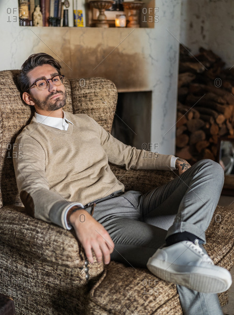 Serious confident man in stylish casual clothes with glasses looking at camera and contemplating while sitting in soft brown armchair against vintage interior