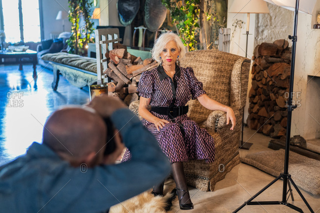 Low angle of professional photographer taking shot with camera of pensive gray haired lady in elegant dress standing against vintage rustic interior among off lighting equipment in photo studio