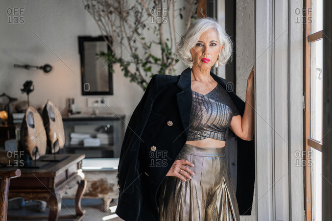 Low angle of confident elderly lady in stylish black jacket and golden shirt and trousers looking at camera while standing with hand on hip and leaning on window frame against blurred luxurious retro interior with antique furniture at home