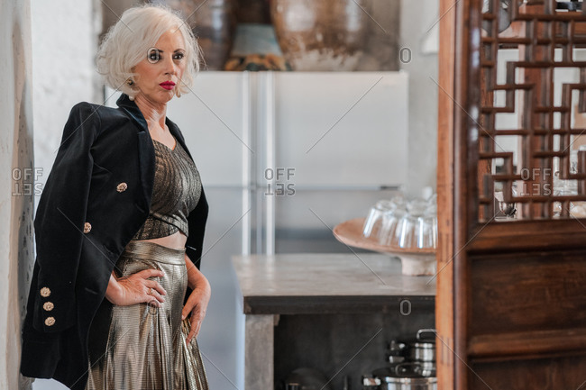 Serious confident female in elegant black jacket and golden shirt and trousers looking away and contemplating while standing with hand on hip beside wooden door against blurred kitchen interior at home