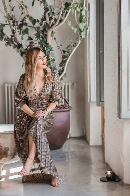Gorgeous adult female in stylish gray dress sitting with legs crossed on edge of old shabby bathtub and looking at camera with interest against green potted tree and white walls in light spacious bathroom