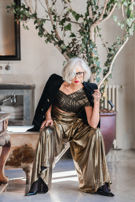 Calm senior confident lady in glasses and elegant clothes looking at camera while sitting on shabby bathtub edge among rich retro interior including old furniture and big green plotted tree in spacious room of country house