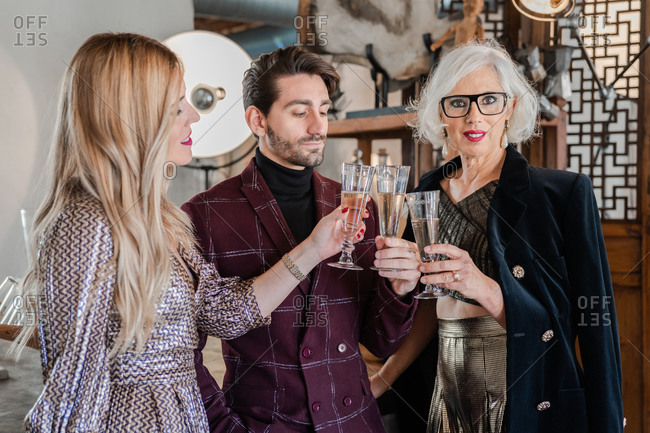 Pensive senior woman in stylish clothes and adult children congratulating each other with family event while drinking champagne together at home