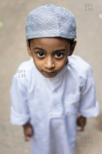 January 25, 2019: Bangladesh January, 25 2019: From above little ethnic boy in traditional Muslim clothes looking at camera while standing on town street