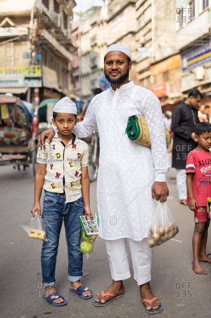 January 25, 2019: Bangladesh January, 25 2019: Ethnic father and kids in traditional Muslim clothes smiling while standing on weathered town street together
