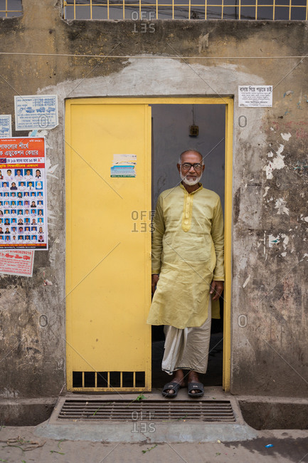 January 25, 2019: Bangladesh January, 25 2019: Full body senior ethnic male in traditional clothes and glasses standing in open doorway of weathered building in town