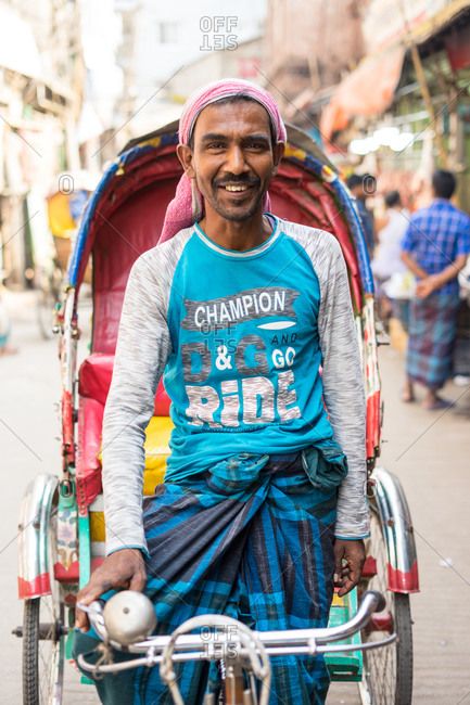 January 25, 2019: Bangladesh January, 25 2019: Cheerful ethnic man in casual clothes smiling and looking at camera while driving traditional rickshaw on town street