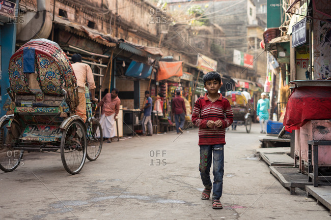 January 25, 2019: Bangladesh January, 25 2019: Poor ethnic boy in dirty clothes looking at camera while walking on asphalt road on weathered street market in town