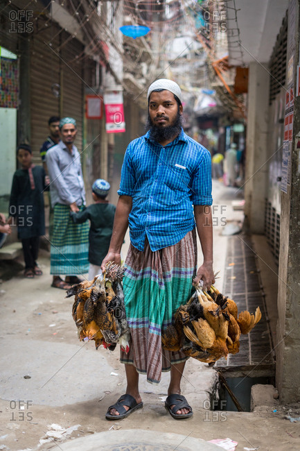 January 25, 2019: Bangladesh January, 25 2019: Bearded ethnic man with bunches of dead chickens standing on shabby street in city