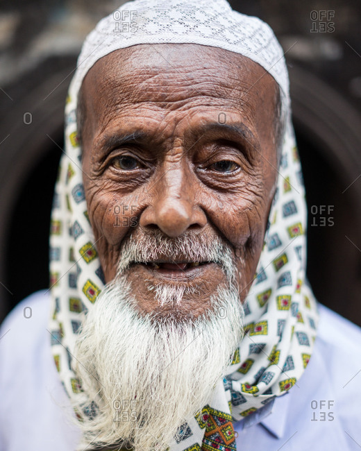 January 25, 2019: Bangladesh January, 25 2019: Senior ethnic male in traditional headgear smiling and looking at camera on street