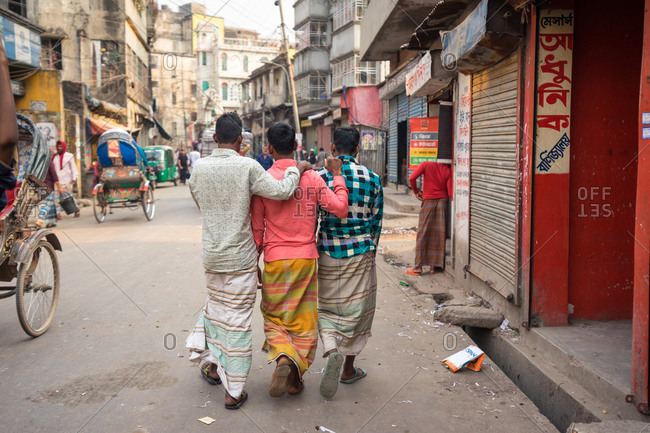 January 25, 2019: Bangladesh January, 25 2019: Back view of ethnic male friends in traditional garments embracing each other while walking on dirty street in city