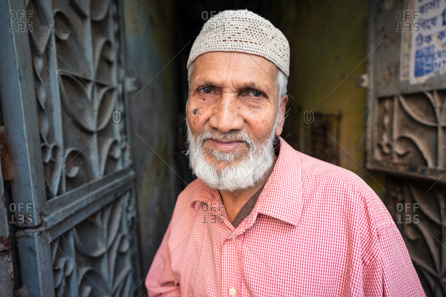 January 30, 2019: Bangladesh January, 30 2019: Senior ethnic man in traditional hat looking at camera while standing outside old building on street