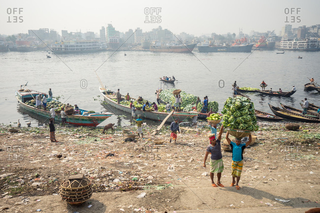 January 20, 2019: Bangladesh January, 20 2019: Group of ethnic people unloading wooden vessels with fruits on polluted shore in city harbor