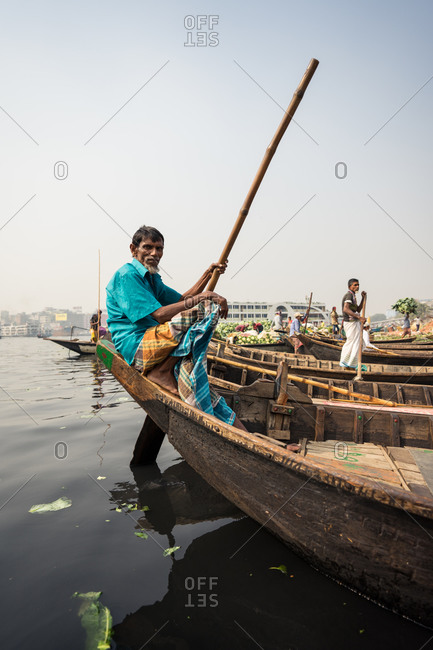January 20, 2019: Bangladesh January, 20 2019: Side view of ethnic man with pole sitting on shabby boat against gray sky in town port