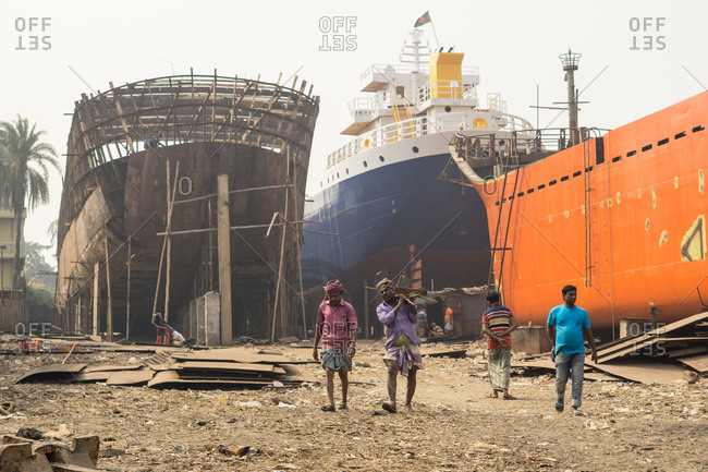 January 20, 2019: Bangladesh January, 20 2019: Group of ethnic men walking and carrying materials neat ships under construction in port