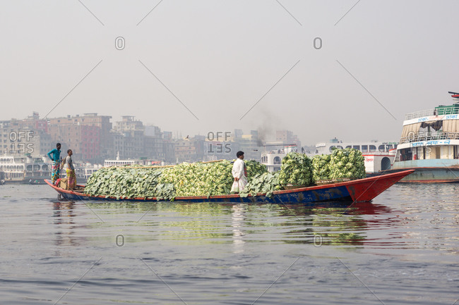 January 20, 2019: Bangladesh January, 20 2019: Group of ethnic people standing on boat loaded with fruits during ride on city river