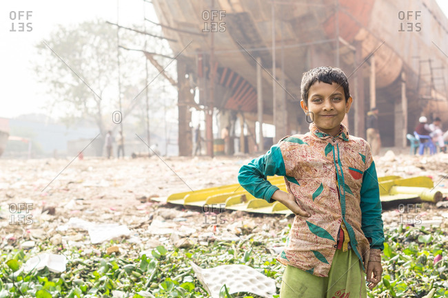January 20, 2019: Bangladesh January, 20 2019: Positive ethnic boy in traditional clothes keeping hand on waist and looking at camera while standing near ship under construction in port
