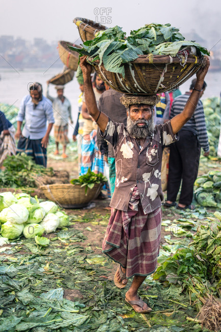 January 24, 2019: Bangladesh January, 24 2019: Full body ethnic people carrying containers and arguing while sorting fresh cabbage in city harbor