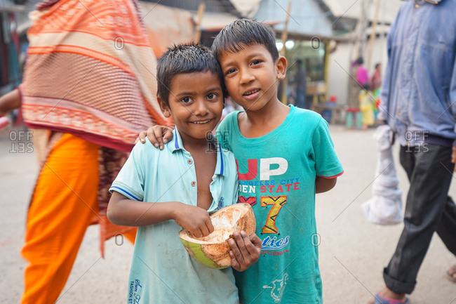 January 19, 2019: Bangladesh January, 19 2019: Little boy hugging cheerful brother with coconut while standing on crowded city street