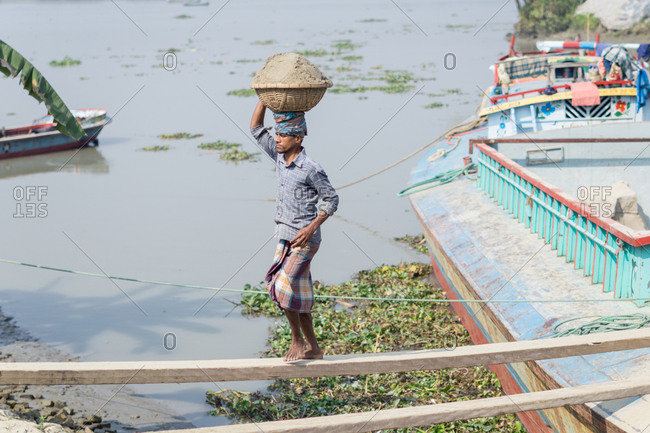 January 23, 2019: Local ethnic people unloading fish from boat after fishing in Barisal in Bangladesh