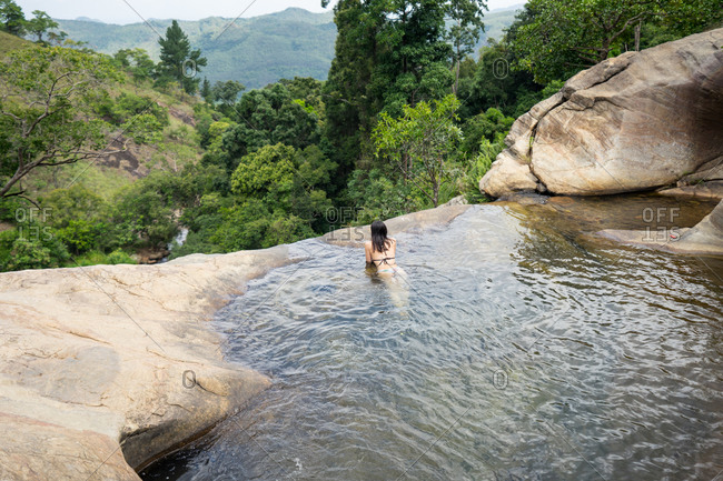 From above relaxed woman in swimwear swimming in crystal water of mountain waterfall in Diyaluma Falls, Sri Lanka