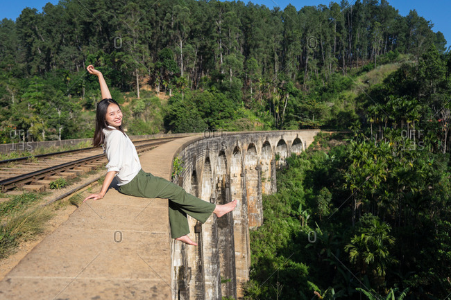 Relaxed Asian woman sitting on bridge dangling legs and waving hand