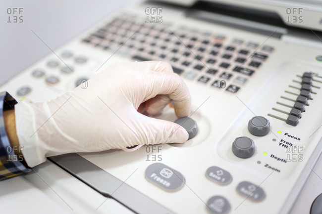 Crop hand of professional doctor in protective gloves setting up diagnostic equipment while examining patient in clinic