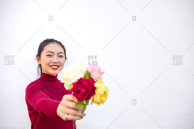 Asian lady showing rose bouquet at camera
