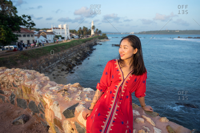 Satisfied Asian female on vacation in colorful light dress sitting on rocked fence of tropical quay and looking away at Galle at Sri Lanka