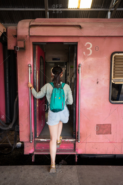 Back view of black haired unrecognizable female traveler in casual wear boarding vehicle train at Colombo train station at Sri Lanka
