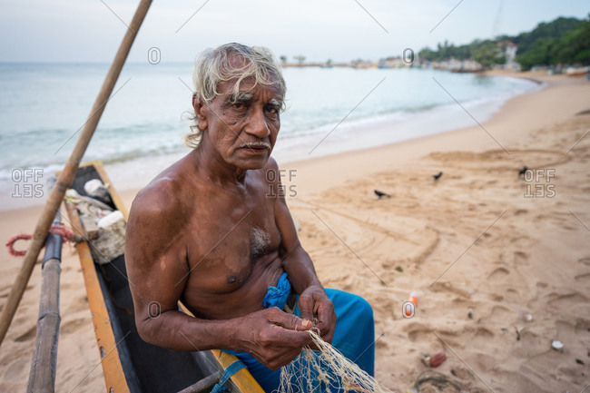 July 28, 2019: Tangalle, Sri  28, 2019: Side view of ethnic old fishermen in casual light wear unwinding fishing net on big yellow boat at tropical sandy beach