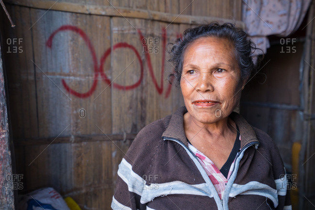 August 14, 2018: Timor  14, 2018: High angle of calm elderly ethnic female in casual clothes looking away with interest while standing at entrance of wooden hut