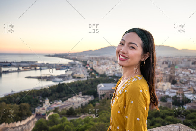 Side view of optimistic Asian lady smiling and looking at camera while visiting Castillo Gibralfaro on blurred background of coastal city and sundown sky in Malaga, Spain
