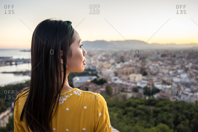 Ethnic tourist against city and sunset sky