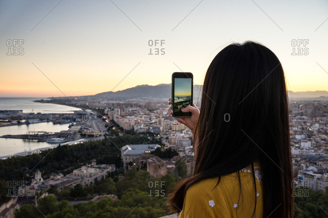 Back view of anonymous woman using smartphone to take photo of coastal town and cloudless sundown sky while visiting Castillo Gibralfaro in Malaga, Spain