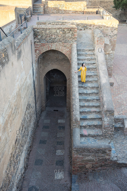 From above woman in yellow dress walking down old staircase of Castillo Gibralfaro on sunny day in Malaga, Spain