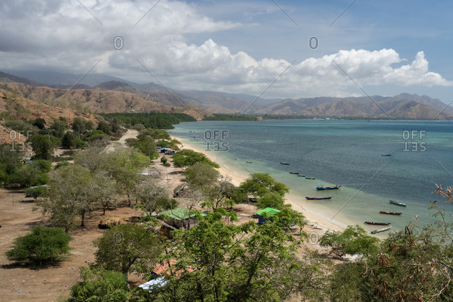 From above picturesque scenery of settlement among green trees on sea shore with boats moored on shallow water against amazing highland coastline under blue sky with lush white clouds in East Timor