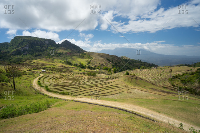 From above beautiful rural environment including terraced fields against solitary settlement on hill under blue sky with lush white clouds in summer in Southeast Asian