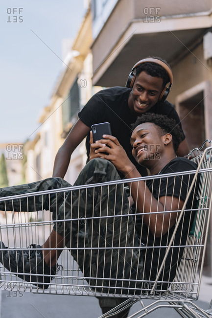 Happy young African American man in casual clothes sitting in cart and sharing messages on smartphone with black male friend in headphones during pastime together in street